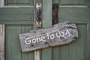 Gone to USA sign on old green door.
